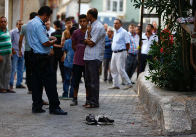 A police officer secures the scene of an explosion as locals stand next to him after a suspected suicide bomber targeted a wedding celebration in the Turkish city of Gaziantep